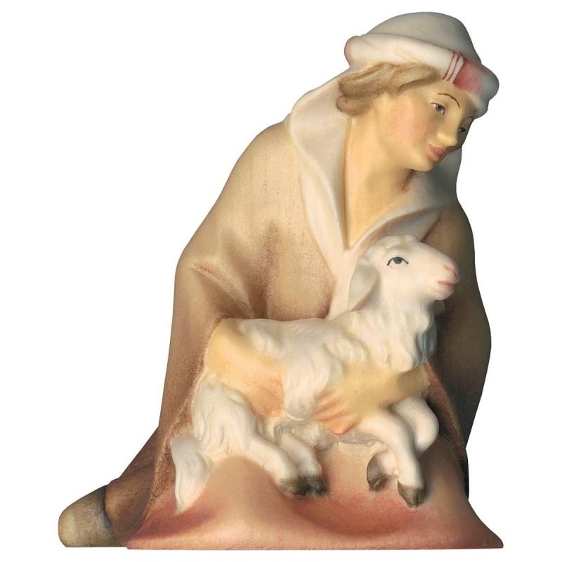 Pastore inginocchiato con agnello